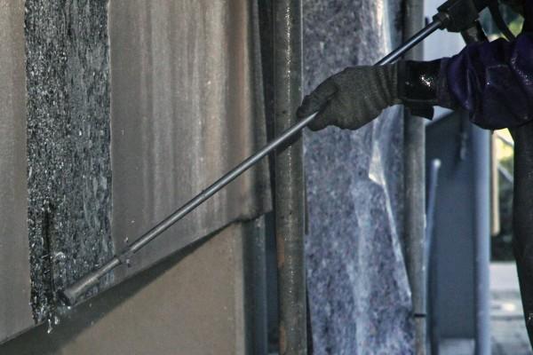 Altbeschichtung an einer Betonfassade entfernen und Bewehrungseisen freilegen