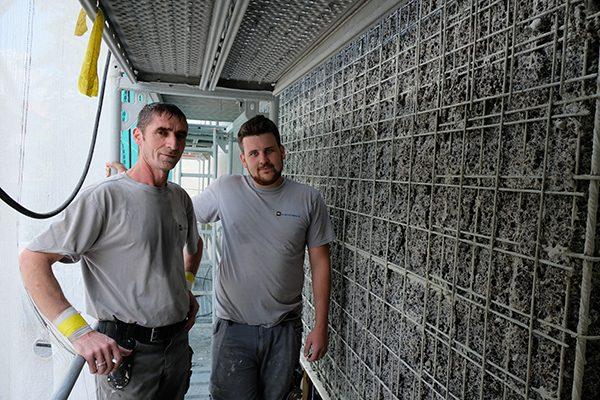 Ramadan Syla und Timo Raißle (v. l.) vor gestrahlter Betonfassade.