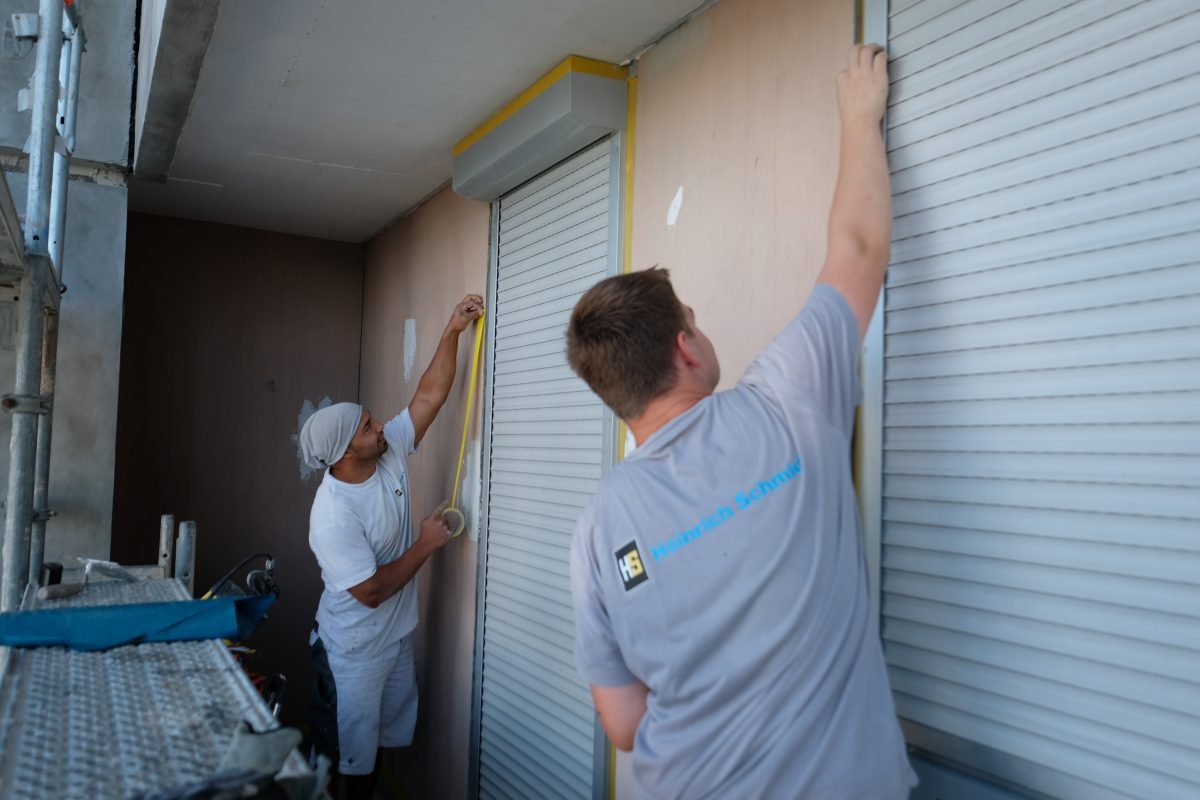 Mohammad Salari (l.) und Kai Günter beim Abkleben der Balkone. Rund 15 Mitarbeiter waren durchschnittlich vor Ort.