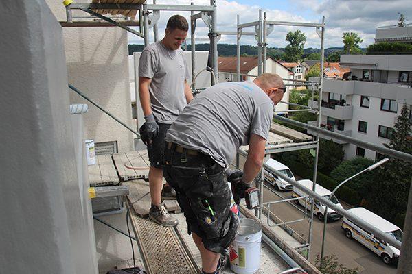 Marco Hoffmann und André Fischer rühren Kunstharzversiegelung an. Damit beschichten sie die Balkone des Wohnhauses. Anschließend werden noch Chips eingestreut.