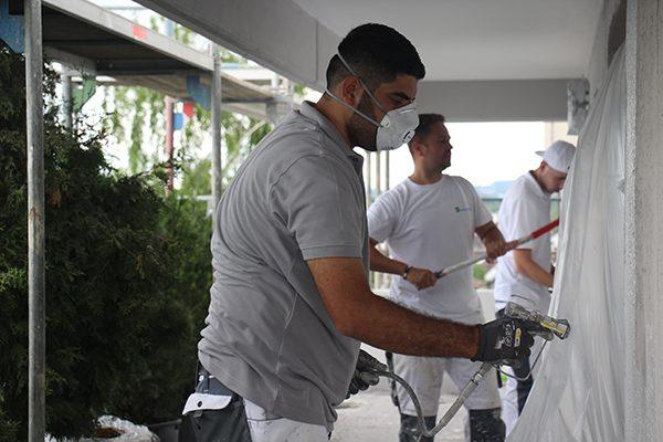 Yasin Yildiz und seine Kollegen Gyorgy Gal und Maik Chromik beim Beschichten der Fassade mit dem Airlessgerät (v. l.).