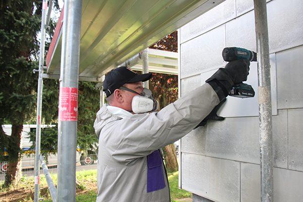 Arbeitsgruppenleiter Markert Eugen beim Austausch der Fassadenplatten.